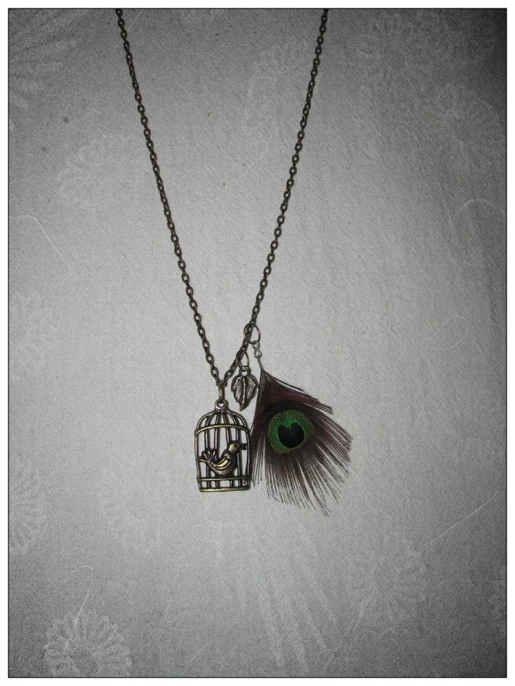 collar con dije de jaula, hoja y pluma de pavo real