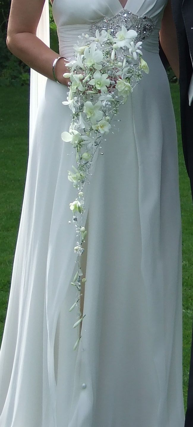 Beautiful ornate cascade trailing wedding bouquet of white dendrobium orchids, with crystal and bead accents.    www.blackbaccara.co.uk