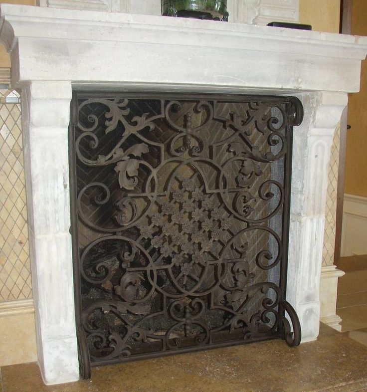 Elegant custom fireplace is complimented by this single panel fireplace screen with lattice and scroll combination.  Built for this Southern California home by Noble Forge, artisan blacksmith in North Hollywood.