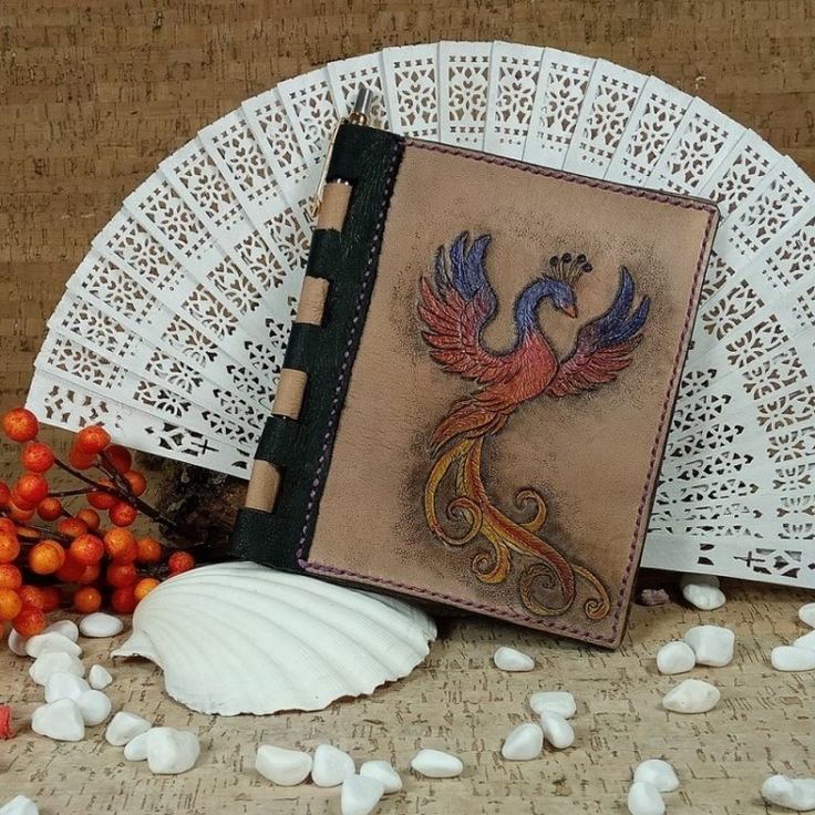 Phoenix Refillable Notebook (No Shipping Costs - In stock) Custom handcrafted leather refillable notebook cover. Holds A6 size paper sheets and the hinged spine is made to hold a pen. The notebook cover is decorated on the front with a lovely hand carved, hand painted Phoenix Rising in purple, red/orange and yellow. On the inside is lined with soft pig skin and Chicago screws are used to hold the A6 pages in place so that new pages can be added/replaced as needed.#b2zoneservice