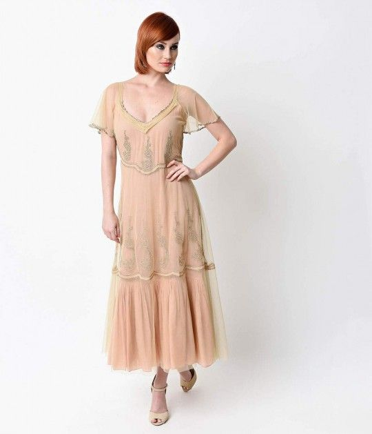 We hope you're comfortable with compliments, dear. A heavenly 1930s inspired dress from Nataya, in a delicate embroidered nude  tulle set against peach muslin for a refined, feminine look. Boasting stunning lace work throughout, a simple tea-length hem an