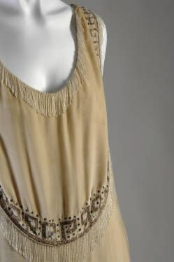 1926.Dress, evening-style, of off white velvet with rhinestone and bead trim. Deep scoop neckline trimmed with crystal bead fringe; sleeveless. Pattern pieces make dress appear to have five overlapping layers, each edged with crystal bead fringe and crystal bead and rhinestone Greek key pattern. Falls just below knee.