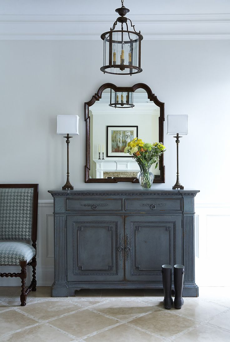 Wedgewood Blue Distressed Look Dresser, White lamps, Dark framed mirror and a byzantine chandelier, blue white chair .. all in perfect balance.