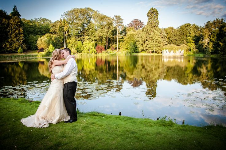 Bride and groom in front of the lake at The Orangery with the boat house in the background. (photo re-edited in 2014)