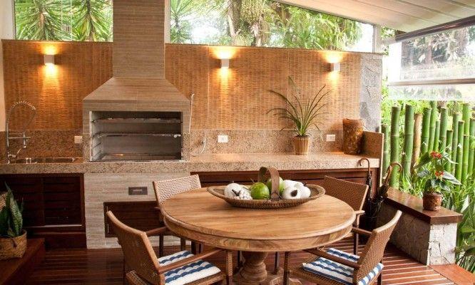 Na outra ponta do ambiente, a churrasqueira de concreto revestida de cerâmica filetada. Na mesa, estampa dos assentos também remete ao ambiente da praia