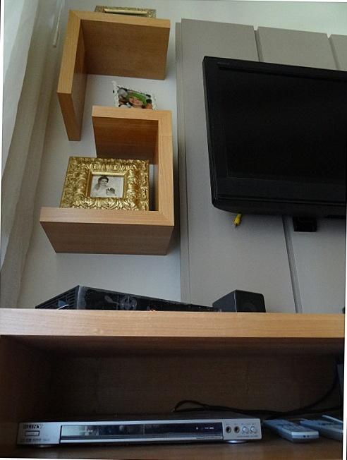 Detalle de panel ranurado lacado con repisas en voladizo enchapadas en madera natural.