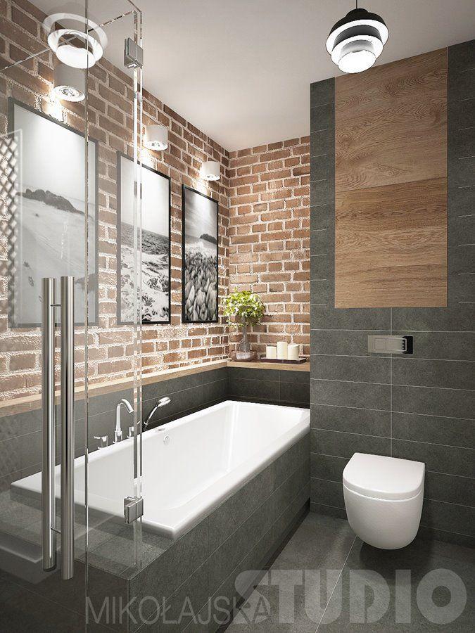 Połączenie płytek w szarościach na ścianie oraz prostokątnej wannie, razem z cegłą i drewnianymi motywami- industrialna łazienka z wanną i prysznicem.