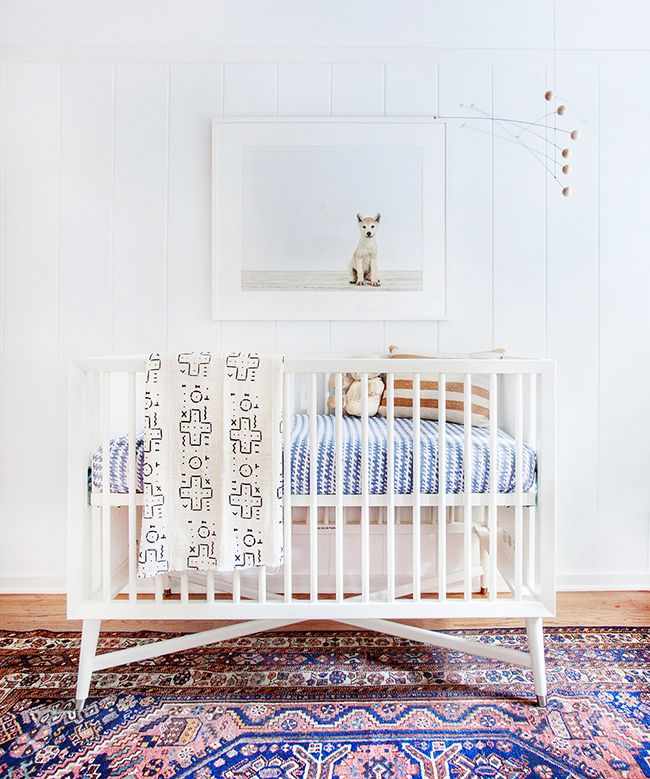 Nursery with white crib, animal photography, and traditional rug