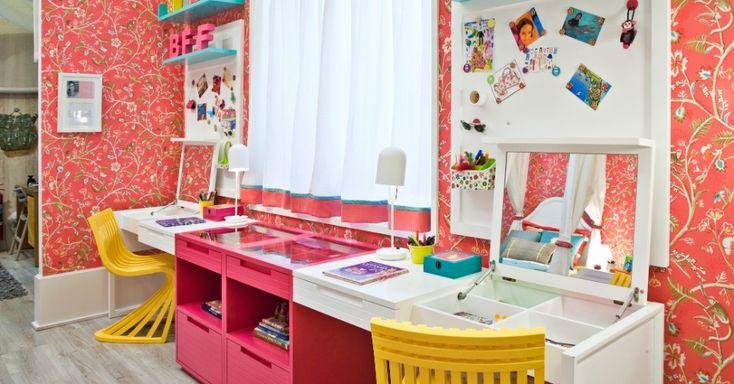 A bancada de estudos no projeto da arquiteta Carla Barranco para a mostra Casa Pronta é compartilhada e delimitada pelo nicho rosa choque. O tampo do móvel se abre trazendo versatilidade à proposta. As cadeiras amarelas e as prateleiras azuis se contrapõem ao papel de parede vermelho