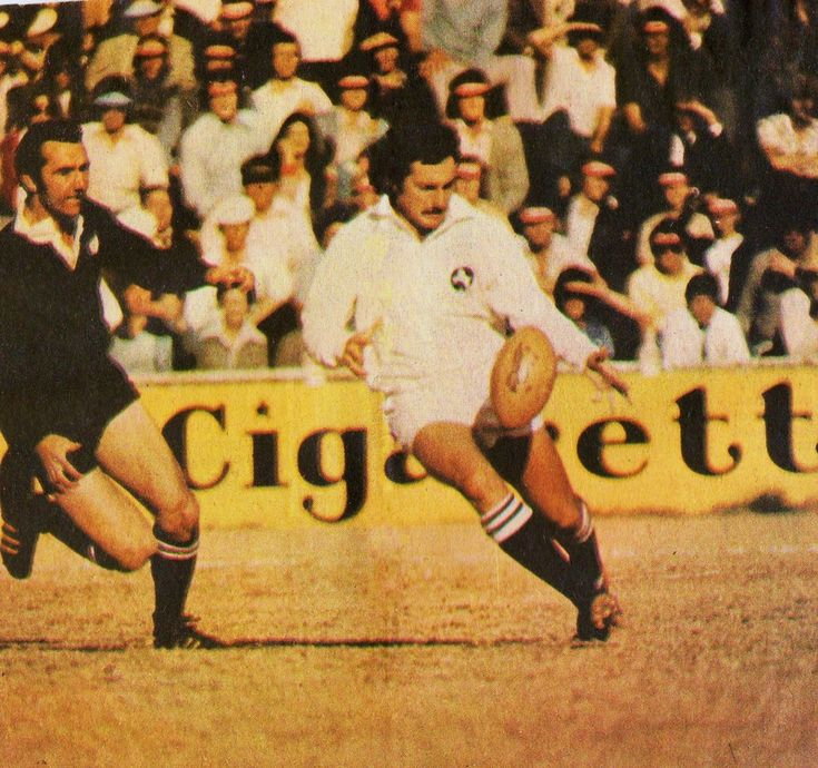 10 July 76 - SA Invitation XV 24 / All Blacks 31  Gavin Cowley in process of executing a chip kick with Andy Leslie in pursuit. Cowley bamboozled the All Blacks with his foot work.