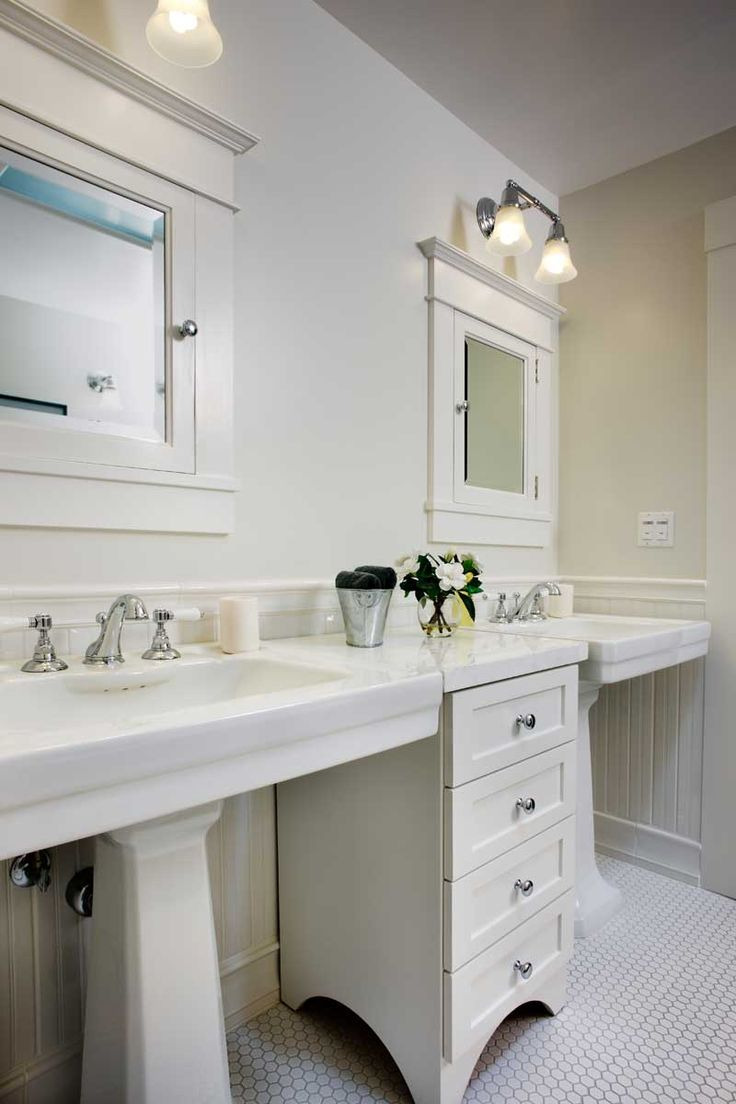 In the guest bath, twin pedestal sinks flanking a narrow chest of drawers and recessed medicine cabinets are space-efficient period elements.