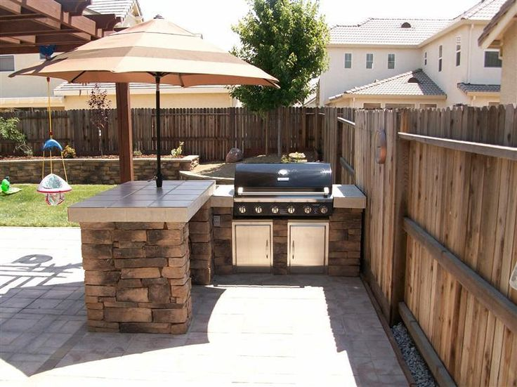 outdoor entertaining area love the stone base built in grill and umbrella