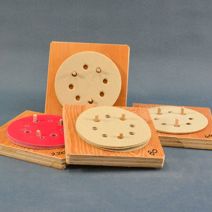 """I am always heading out the door with a handful of sanding discs which are often unsorted and reading the numbers on the back can be sketchy with poor printing, holes etc. The solution for this was using a piece of waste wood, like 3/4"""" plywood, 6 inches square and inserting dowels in it to help keep the sanding disc aligned, is a great solution. #woodworking #DIY"""