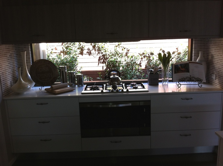 Kitchen with window splashback over stove and benchtop.