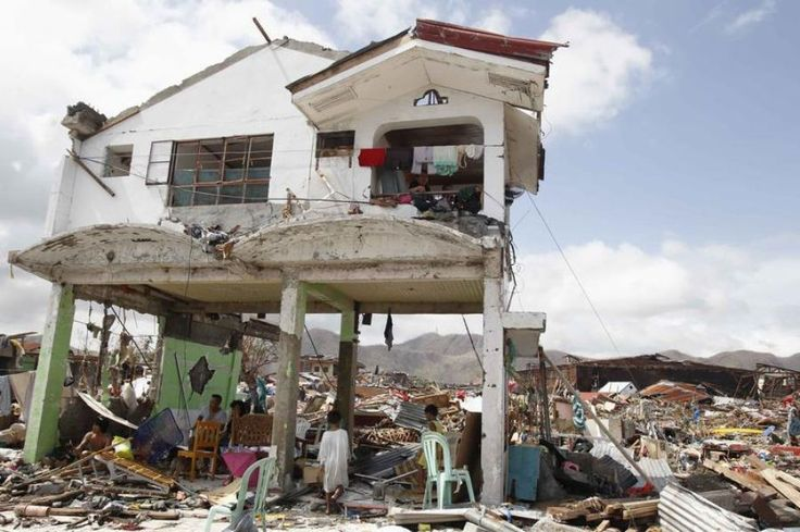 Des survivants restent dans leur maison endommagée à Tacloban.
