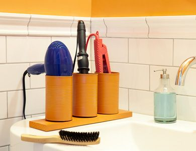Paint clean soup cans any color, then screw them to a piece of wood. Set the unit in the bathroom to store cooled hair-styling tools, or the kitchen for cooking utensils