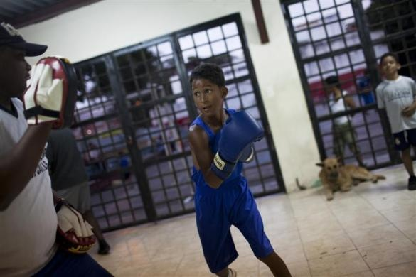 Jonathan Zarramera, 12, practises Olympics-style street boxing with his coach during a training session at a gym in the low-income neighborhood of Propatria in Caracas February 8, 2011.  REUTERS/Carlos Garcia Rawlins