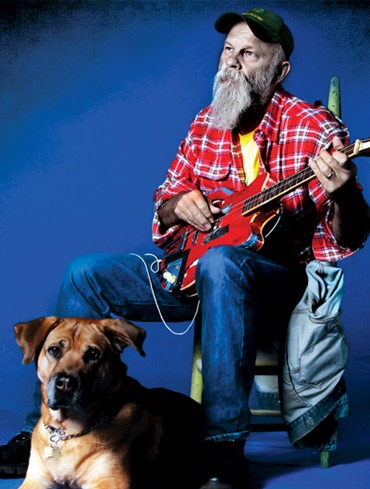 Seasick Steve with his dog, and one of his favorite guitars.