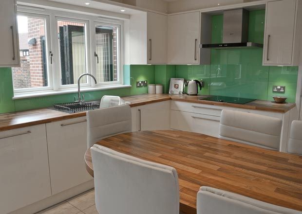 Professionally Installed Kitchens at Dobsons. Gloss white kitchen with Butchers Block laminate worktop and turquoise/green glass splashback