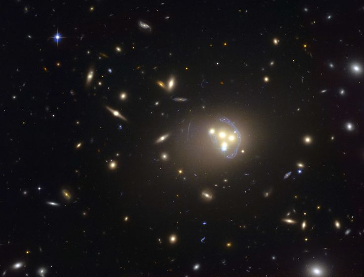 A handout photo from the #NASA/ESA #Hubble #Space #Telescope released on April 13, 2015 by the #European Southern #Observatory shows the rich #galaxy cluster Abell 3827. The strange blue structures surrounding the central galaxies are gravitationally lensed views of a much more distant galaxy behind the cluster. AFP PHOTO / HO / EUROPEAN SOUTHERN OBSERVATORY