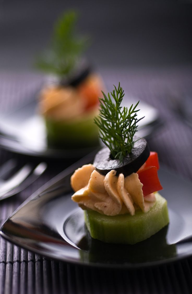 Chilled salmon mousse on cucumber with black olive and pimiento garnish