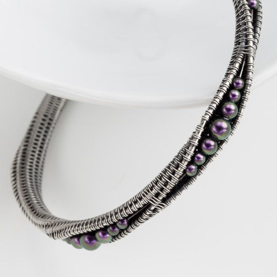 Made from fine silver and sterling silver wire that has been woven and twisted together. The bracelet has an inner diameter of 7.5 inches and is 3/8 inches wide. Nestled inside each split are Swarovski Pearls  The bracelet has been antiqued to accentuate the texture of the weave and the movement of the wire.