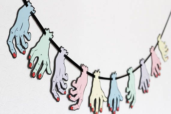 This is one of our absolute favourites! Our severed hand garland is a two layer paper cut design, each garland has 10 hands in 5 colours. It comes in two sizes, 5 (as seen in the images) and 7 high, and will add masses of fun and interest to any space! You will receive them pre strung onto black double satin ribbon, the small size measures 39 in length and the large measures 78 long  All our designs are our own, hand drawn and then produced in our studio in Margate, England.  We are happy to…
