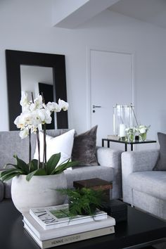 White bowl of orchids on coffee table on top of large coffee table book. Vessel can be fuller with more flowers.