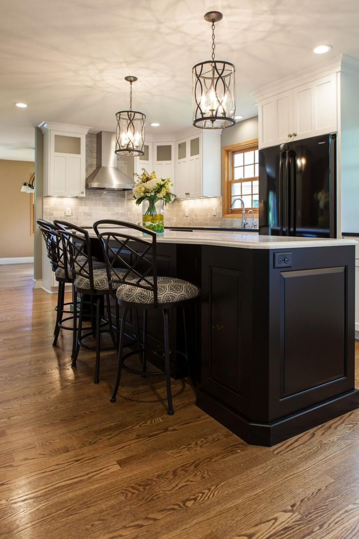 This clean and classic neutral kitchen boasts black leather granite on the perimeter and a simulated white Carrara quartz on the island for easy maintenance. The existing oak floors were kept and stained darker to update the look.