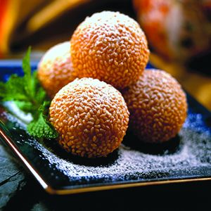 Chinese dessert: Dragon Balls-these delicious treats are dough, filled with sweet bean and plum paste, then rolled in toasted sweet sesame seeds, and deep fried. These are actually available in the cold cases of most supermarkets.