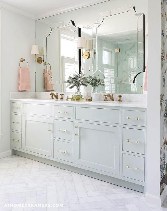 A white marble herringbone tile floor leads to a stunning bathroom boasts a pale gray dual washstand painted Sherwin Williams Contented adorned with brass and glass pulls topped with Alabama White Marble fitted with his and hers sinks and aged brass faucets placed under a full length mirror accented with individual mirrors illuminated by Camille Long Sconces.