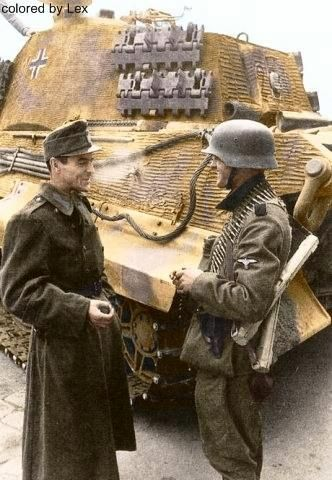"A Hungarian (L) & German (Rt) soldier ""trading war stories"" beside a German Tiger II tank (Henschel turret). Budapest, 20 Oct 1944."
