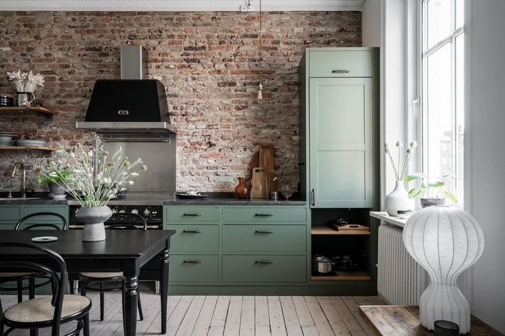 a swedish apartment with a green kitchen and exposed brick