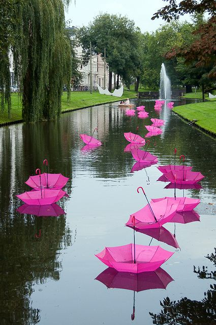 "Luke Jerram 2010 art installation. For a festival in the Netherlands, 1000 brightly colored umbrellas were placed upside-down into the calm long canal that winds through part of Rotterdam. Titled ""Just Sometimes...,"" the artwork was intended to be read as a gift presented just for a smile, like a bouquet of flowers. Photo by Ed Jansen, de_buurman via Flickr"