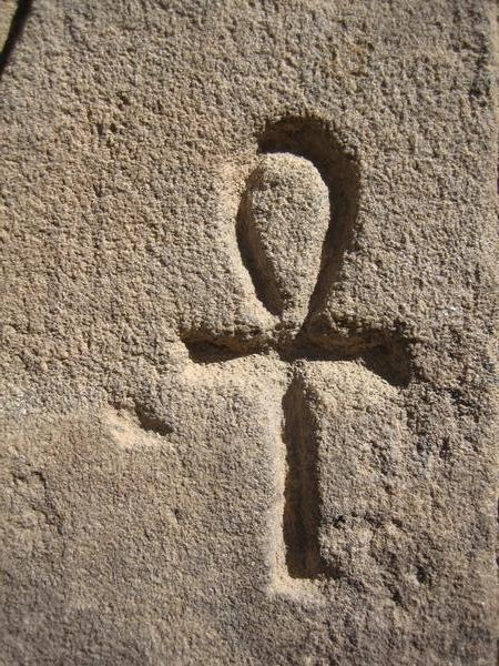 The ankh is an ancient Egyptian symbol of life. Also known as an Ansata (latin; handle) cross, it is a visual representation of a sandal strap. The horizontal and vertical bars of the lower tau cross represent the feminine and masculine energy, respectively. This combination of male and female symbols (the cross and circle) in the ankh suggest fertility and creative power. The top loop also symbolises the sun on the horizon, and suggests reincarnation and rebirth.