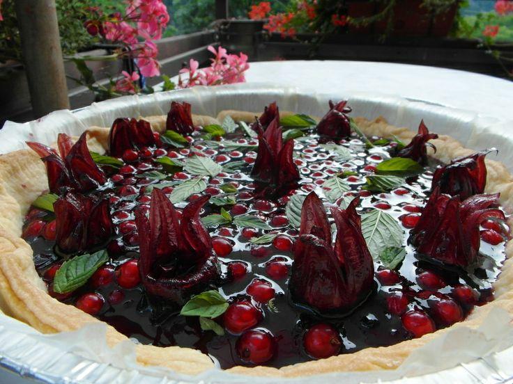 Crostata di ribes rossi con fiori di ibisco e foglioline di menta fresca