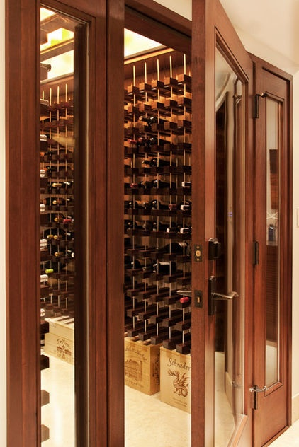 The basement includes a lot of storage, including this large wine cellar. A glass door and sidelights allow the clients to admire their collection from the bar area across from it.