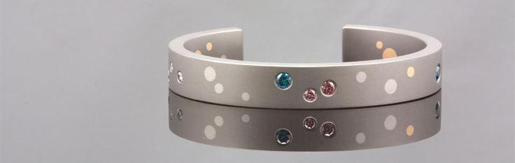 Titanium armband met platina en 18 karaat geelgouden stippen, bezet met roze, blauwe en witte diamant.