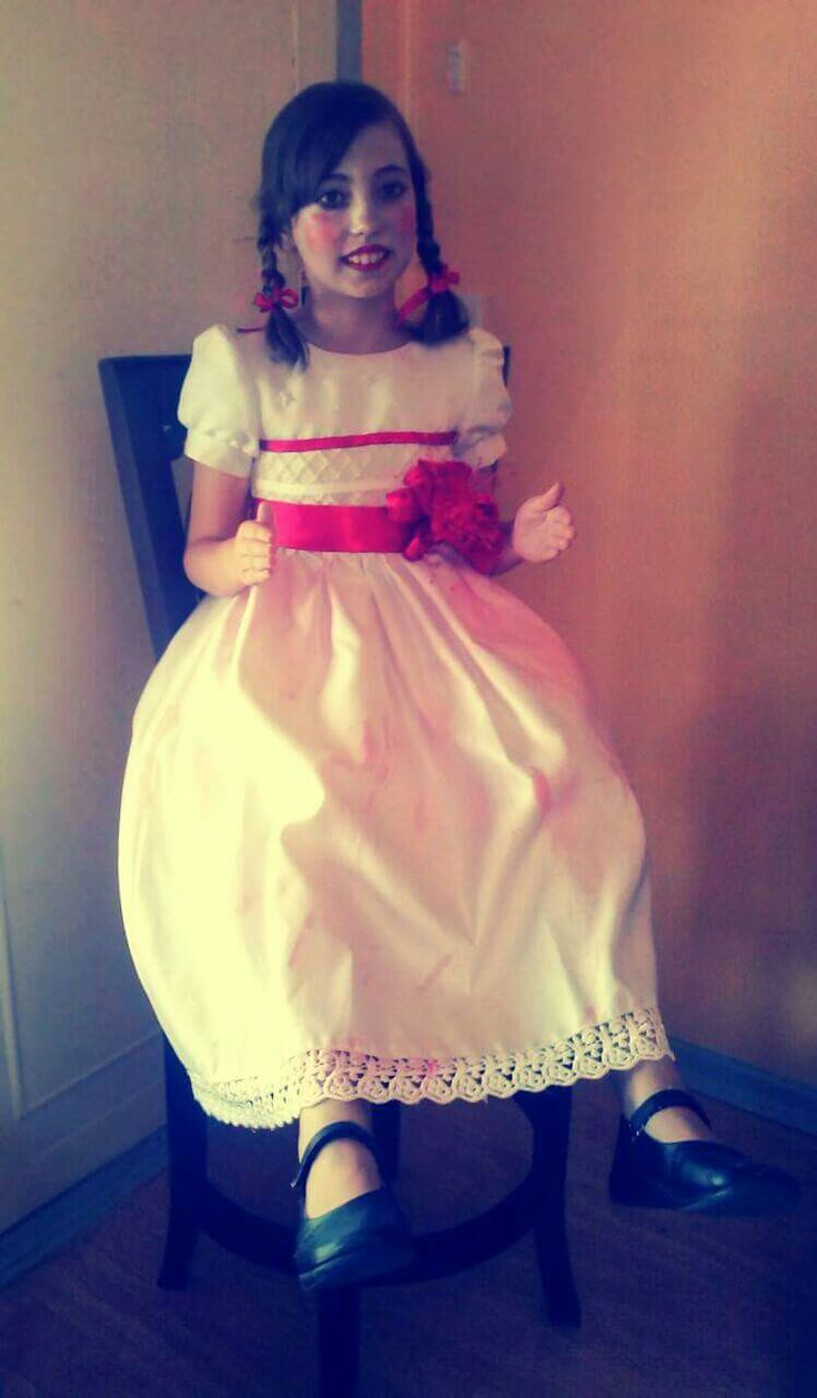 Annabelle Halloween costume. $20- $30 white dress.  Dirty it up. Red ribbon from spotlight. Red plastic flower from $2 shop. Black school shoes. Cheap halloween makeup for a pale face and rosy cheeks. Don't forget the plaits!