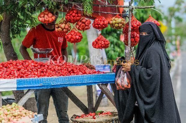 Seorang wanita bercadar membeli jambu lilin yang dijual di kawasan Jalan Iskandar Muda, Meuraxa, Banda Aceh, Kamis (3/4/2014). Pemberlakukan syariat Islam di Aceh, tidak menyurutkan tingkat kunjungan wisatawan. Sejumlah turis asing bahkan terlihat menghormati adat setempat ketika berkunjung ke sejumlah objek wisata.