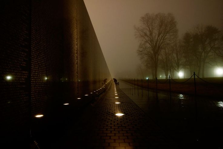 In this powerful photograph by Kevin Wolf, we see a lone figure knelt at the Vietnam Memorial in Washington D.C.