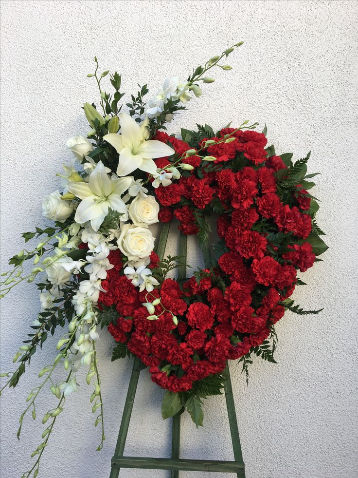 Open heart with the greens large and baby carnations cluster with white Casablanca lilies white roses and orchids