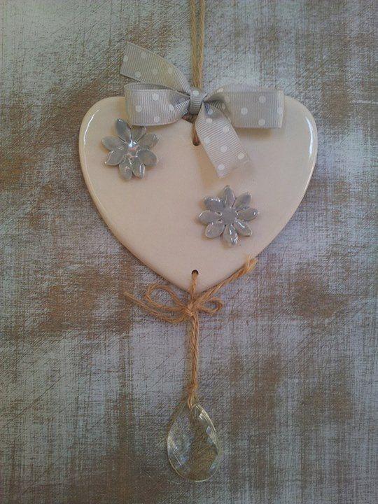 Cuore in ceramica con fiori grigio perla in rilievo.Rifinito con nastro grigio a pois bianchi.Per terminale una goccia di vetro in perfetto stile shabby chic. Bellissimo.