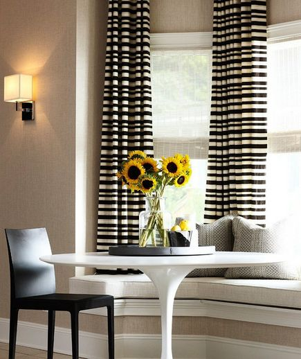 Small dining table, window seat and horizontal stripe curtains.  What a great statement with the sunflowers