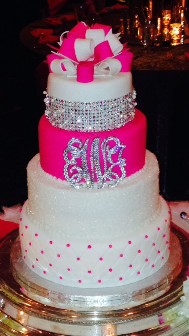 My AMAZING wedding cake!!!! The bottom layer was diamond shapes with pink edible beads at each intersection, the second layer was edible glitter, the third layer was hot pink with our joint monogram, and the top layer had a diamond, pearl, and pink stoned band across it with a pink and white bow adorning the top!!