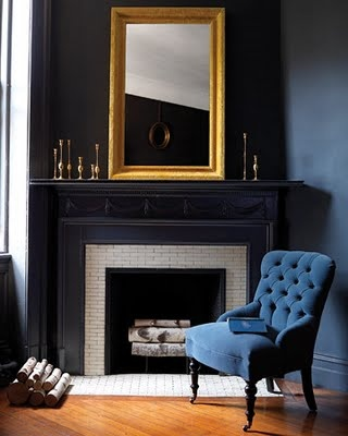 From Martha Stewart Living, this room features a gilt mirror and an indigo blue tufted velvet chair.
