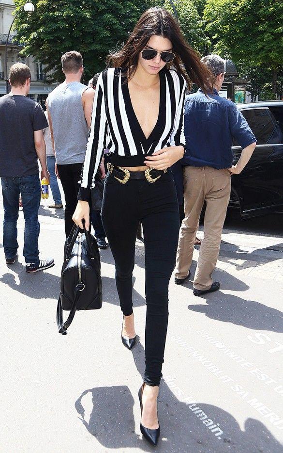 Kendall Jenner wears a striped v-neck crop top, Western-style belt, skinny jeans, pumps, and a black bag