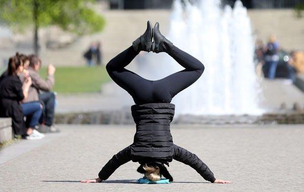 Mulher mostra equilíbrio ao fazer ioga em parque na Alemanha Cena foi registrada por Wolfgang Klumm no parque Lustgarten, em Berlim. Praticante foi fotografada no momento em que estava de cabeça para baixo.