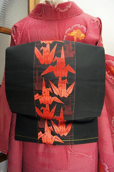 黒地に凛と映える、つややかな銀朱色の折り鶴が縞のように織り出された粋な名古屋帯です。