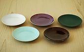 陶器の銘々皿です。 釉薬の異なる「粉引」、「青磁」、「辰砂」、「飴釉」、「織部」の5種をご用意しました。  取り皿にはもちろん、前菜などの盛皿としても最適です。 [釉薬の種類]  粉引(こひき)   「粉吹き」ともいわれ、粉を引いた(吹いた)ように白いことが名前の由来となっています。白磁の白さとは異なり、陶器ならではのやわらかさを持っています。また、焼成時に釉薬の間に入った空気が反応し、ところどころが薄いピンク色に発色します。   青磁(せいじ)   釉薬中に含まれる少量の鉄分が還元焼成によって反応し、青色に発色します。その歴史は非常に古く、遅くとも10世紀初めには使われていたといわれています。   辰砂(しんしゃ)   透明な基礎釉に少量の銅を入れ、還元焼成によって赤色に発色させる釉薬です。   飴釉(あめゆう)   透明釉に鉄またはマンガンを少量加え酸化焼成で焼くことにより、文字どおり褐色の飴のような艶のある色になります。   織部(おりべ)   灰釉に銅を混ぜて作られる釉薬です。千利休の高弟であった古田織部がこの濃緑色を好み、作らせたことが名前の由来となっています。…